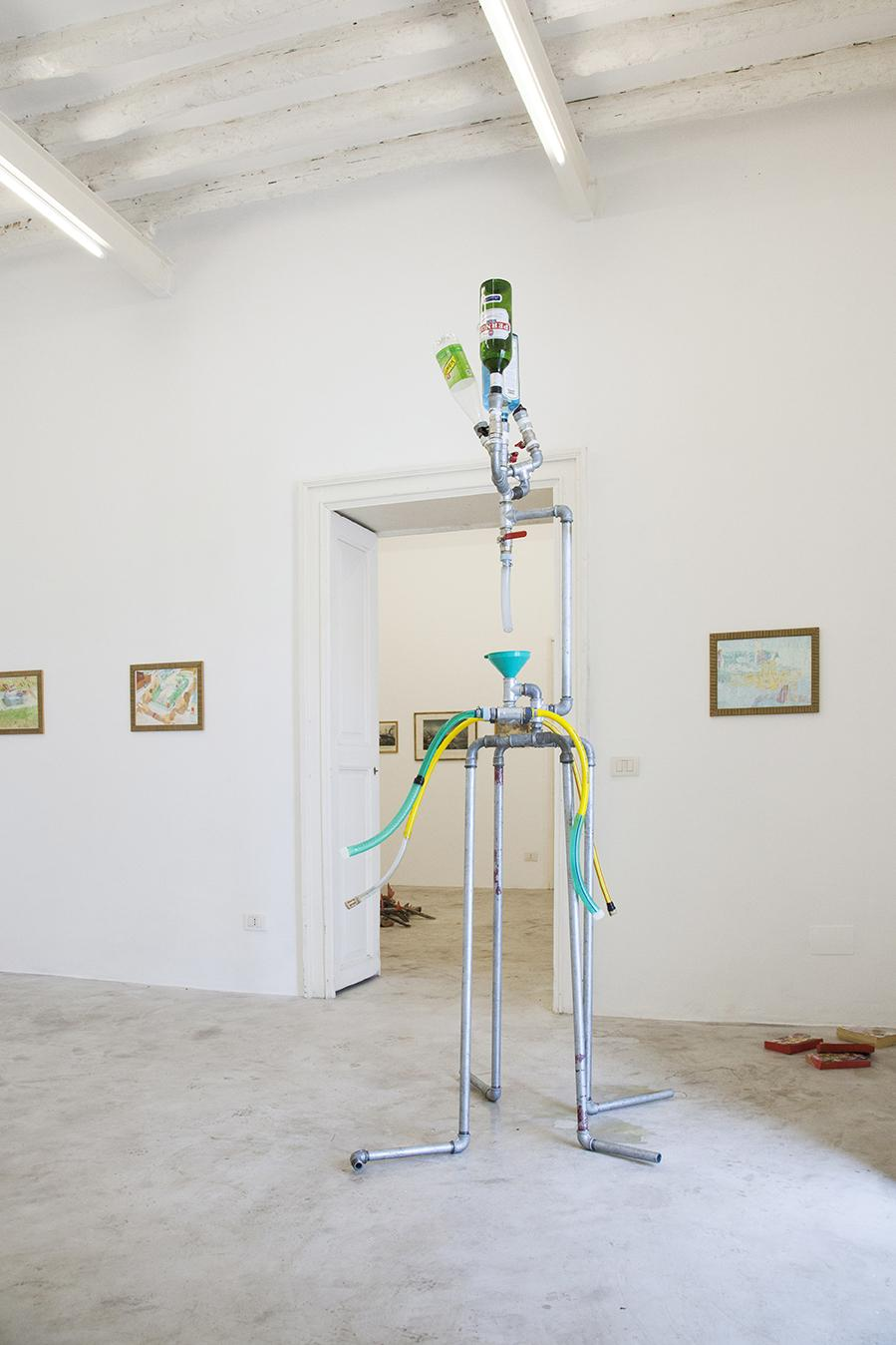 """Giulio Delvè /Moonshining/, 2016 Connections in cast iron, flexible tubes and plumbing equipment, bottles, 220  x 85 x 60cm Installation view """"I Will Go Where I Don't Belong"""" Photo:Giovanna Silva Courtesy Fiorucci Art Trust, London"""