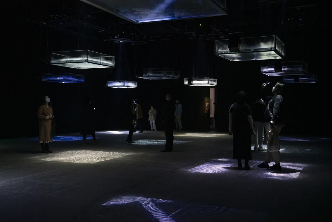 Ryuichi Sakamoto + Shiro Takatani, LIFE - fluid, invisible, inaudible..., 2007/2021, Installation, 24 channel audio, 12 acrylic water tanks with ultrasonic fog generators and video projectors, courtesy M Woods Museum