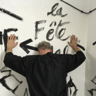 Curator Yann Chevallier in front ofa mural by Vava Dudu