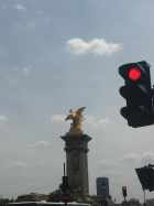 """One of the Pont Alexandre III''s 'fames' or rumours. In Greco-Roman mythology Pheme or Fama was a gossip with """"her feet on the ground, and her head in the clouds, making the small seem great and the great seem greater"""" and lived in a home with 1000 windows so she could hear all being said in the world – at least according to her acolyte Virgil"""